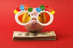 Porcellino salvadanaio con i vetri del partito di buon compleanno che stanno sulla pila di banconote in dollari dell'americano ce Fotografie Stock Libere da Diritti
