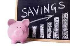 Porcellino salvadanaio con il grafico di risparmio Immagini Stock Libere da Diritti