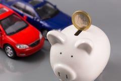 Porcellino salvadanaio con l'euro e le automobili Immagine Stock Libera da Diritti