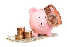 Porcellino salvadanaio con l'orologio di oro e dei soldi isolato Fotografia Stock
