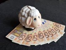 porcellino salvadanaio con la figura di una pecora bianca e delle banconote dell'euro 50 immagine stock