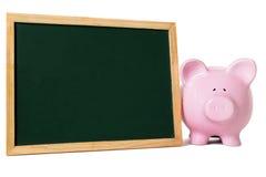 Porcellino salvadanaio con la piccola lavagna in bianco, concetto del fondo di risparmio di istruzione Fotografia Stock