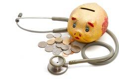 Porcellino salvadanaio con le monete e lo stetoscopio Fotografia Stock