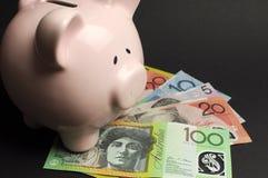 Porcellino salvadanaio con soldi australiani contro un fondo nero Fotografia Stock