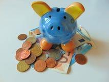 Porcellino salvadanaio con soldi e le monete Immagine Stock
