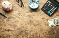 Porcellino salvadanaio con soldi ed il calcolatore sullo scrittorio di legno Salvo i vostri soldi immagine stock