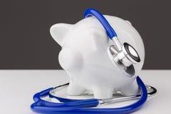 Porcellino salvadanaio con uno stetoscopio Fotografia Stock Libera da Diritti