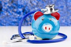 Porcellino salvadanaio con uno stetoscopio: costi medici Fotografia Stock