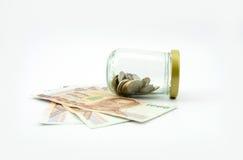 Porcellino salvadanaio della bottiglia di vetro e dei soldi Fotografia Stock