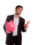 Porcellino salvadanaio della tenuta dell'uomo di affari con soldi Immagine Stock Libera da Diritti