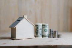 Porcellino salvadanaio di legno della casa con i soldi del dollaro e moneta sulla linguetta di legno Fotografia Stock Libera da Diritti
