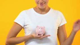 Porcellino salvadanaio di tenuta femminile sorridente, bilancio familiare, risparmio per l'investimento futuro archivi video
