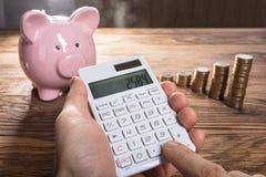 Porcellino salvadanaio e moneta di Person Calculating On Calculator With impilati Fotografia Stock