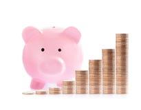 Porcellino salvadanaio e pile rosa di monete dei soldi Fotografia Stock