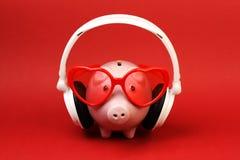 Porcellino salvadanaio nell'amore con gli occhiali da sole rossi del cuore e la cuffia avricolare bianca che stanno su fondo ross Immagine Stock