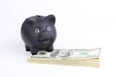 Porcellino salvadanaio nero che sta sulla pila di banconote in dollari dell'americano cento dei soldi su fondo bianco Fotografia Stock