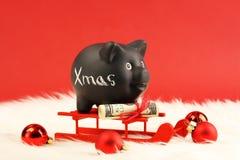 Porcellino salvadanaio nero con natale bianco del testo ed il regalo di soldi con il nastro rosso sulle banconote in dollari dell Immagini Stock Libere da Diritti