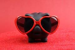 Porcellino salvadanaio nero innamorato con gli occhiali da sole rossi del cuore che stanno sulla sabbia rossa davanti a fondo ros Immagini Stock Libere da Diritti
