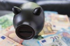 Porcellino salvadanaio nero sul mucchio di euro banconote come concetto di risparmio Fotografia Stock