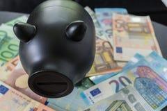Porcellino salvadanaio nero sul mucchio di euro banconote come risparmio finanziario c Immagini Stock Libere da Diritti