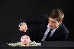 Porcellino salvadanaio rosa che sta sui dollari Fotografie Stock Libere da Diritti