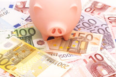 Porcellino salvadanaio rosa circondato dalle euro note Fotografia Stock Libera da Diritti