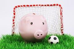 Porcellino salvadanaio rosa con la palla di calcio sul campo verde con il portone su fondo bianco Immagine Stock