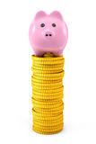 Porcellino salvadanaio rosa sopra le pile dorate della moneta del dollaro Immagine Stock Libera da Diritti