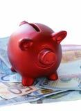 Porcellino salvadanaio rosso con le euro banconote Immagini Stock