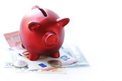 Porcellino salvadanaio rosso con le euro banconote Fotografia Stock Libera da Diritti