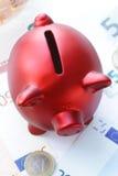 Porcellino salvadanaio rosso con le euro banconote Fotografia Stock