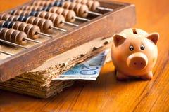 Porcellino salvadanaio su una tavola vecchio dal bankno del libro, dell'abaco e dell'euro 20 Fotografia Stock