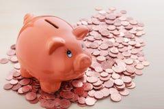 Porcellino salvadanaio sul mucchio delle monete degli euro centesimi Fotografia Stock