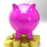 Porcellino salvadanaio sulle monete che mostrano il risparmio Immagini Stock Libere da Diritti