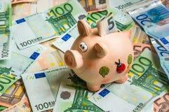 Porcellino salvadanaio in un mucchio di euro soldi Fotografie Stock