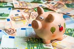 Porcellino salvadanaio in un mucchio di euro soldi Immagine Stock Libera da Diritti