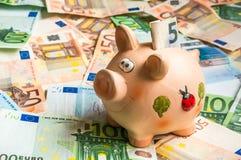 Porcellino salvadanaio in un mucchio di euro soldi Immagini Stock Libere da Diritti