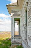 Porch of Abandoned House. The porch of an old white abandoned house on a beautiful day. Vertical orientation royalty free stock photography