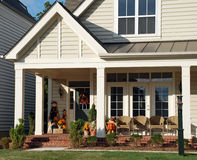 Porch in Autumn. The porch of a luxury home decorated with wreaths, pumpkins and scarecrows, and made comfortable by wicker chairs Stock Images