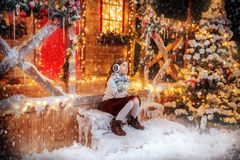 Porch of house at christmas. A cute girl is sitting on the porch of the house decorated for Christmas and holding a gift box. Merry Christmas, Happy New Year stock images