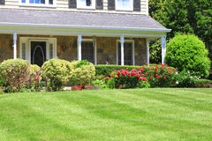 Landscaping. House with porch and flowerbed landscaping