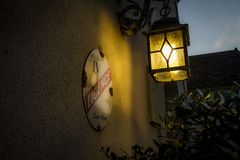 Porch Lantern, French Chateau. A porch lantern at a chateau near Le Mans, France glows a dusk in summer,  June 2015 Royalty Free Stock Image