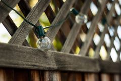 String of Porch Lightbulbs. A string of lightbulbs hang from a fence surrounding a porch in summer royalty free stock images