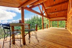 Porch of the log cabin with small table. Royalty Free Stock Image