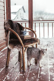 Porch of log cabine with snow. Chair with fur cover on a porch deck of a log cabin with snow. Tea, warm blanket, reading and cat. Cold winter relax weekend royalty free stock image