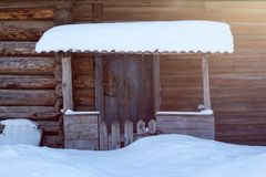 Porch of the house after snowfall. The porch of the old wooden houses bathed in sunshine after a snowfall Stock Photos