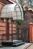 Porch with railings. Porch with railing and canopy from the rain at the outer door of the house of red brick Stock Photo