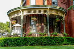 Porch at a Victorian Brick Bed and Breakfast Home. Victorian Brick Bed and Breakfast Home, Queen Anne archictecture with beautiful landscaping in Lexington Stock Photo