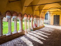 Arched porch with white stone columns in the courtyard of a Bene. Porch with white stone columns in the courtyard of a Benedictine abbey Royalty Free Stock Image