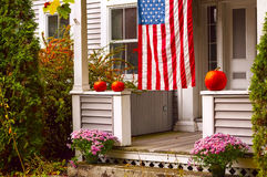 Porch of a wooden house decorated for Halloween and the American flag. Wonderful autumnal view of flowers on the steps with autumn leaves Stock Photos